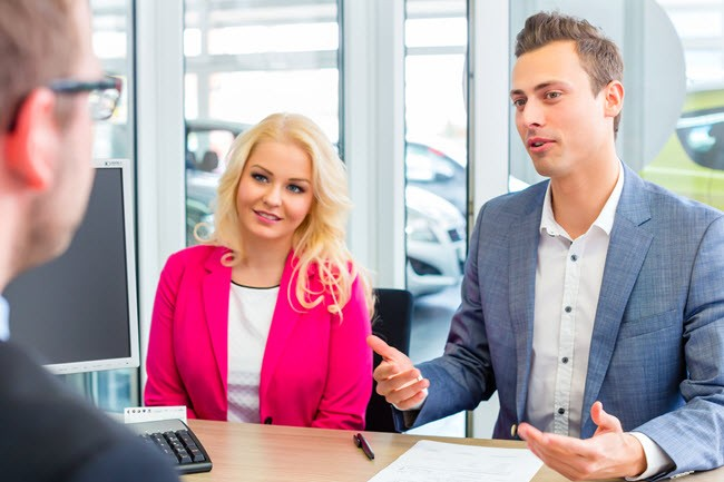 man and woman negotiating a new car purchase